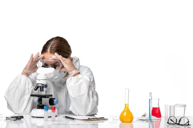 Medico femminile di vista frontale in vestito speciale e maschera da portare che lavora con il microscopio su fondo bianco coronavirus pandemico del virus covid
