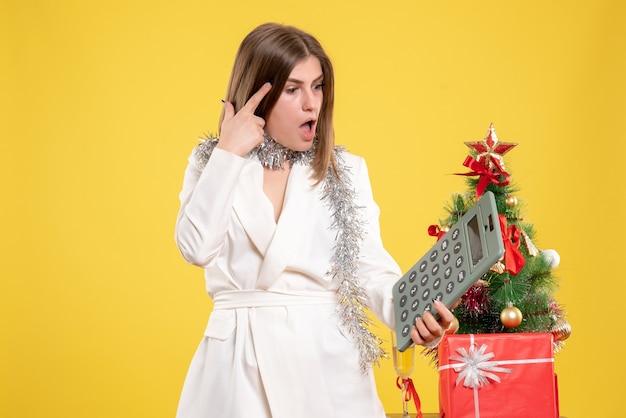 Вид спереди женщина-врач, стоящая и держащая калькулятор на желтом фоне с рождественской елкой и подарочными коробками