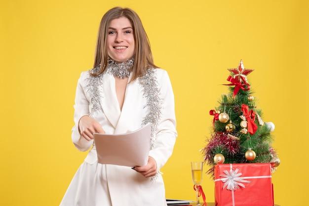 Вид спереди женщина-врач, стоящая и держащая документы на желтом фоне с рождественской елкой и подарочными коробками