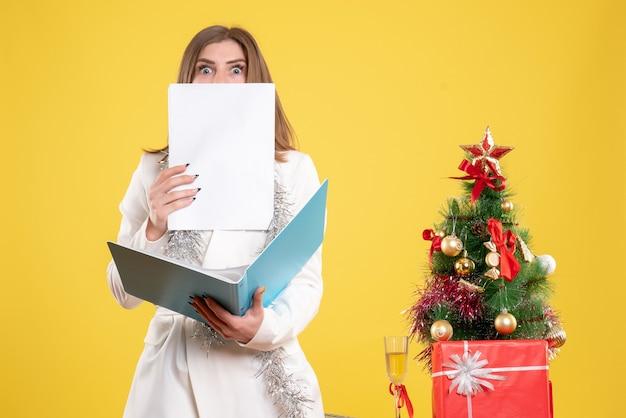 クリスマスツリーとギフトボックスと黄色の背景に立ってドキュメントを保持している正面図の女性医師