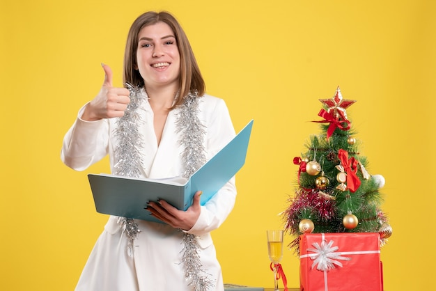크리스마스 트리와 선물 상자와 노란색 책상에 서서 문서를 들고 전면보기 여성 의사