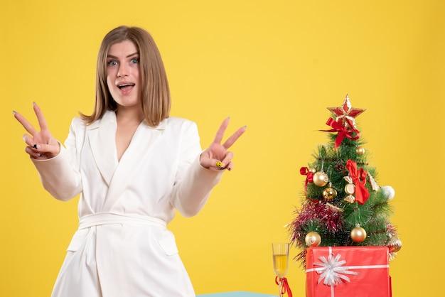 노란색 배경에 작은 크리스마스 트리와 테이블 주위에 서있는 전면보기 여성 의사