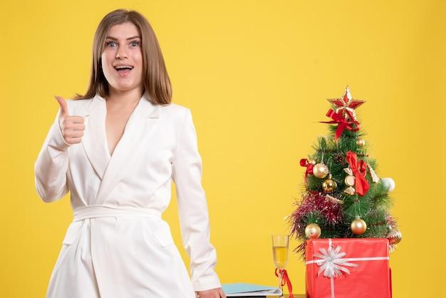 Medico femminile di vista frontale che sta intorno al tavolo con il piccolo albero di natale su fondo giallo con l'albero di natale e le confezioni regalo