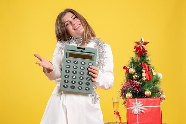Vista frontale medico femminile in piedi e tenendo il calcolatore su sfondo giallo con albero di natale e confezioni regalo