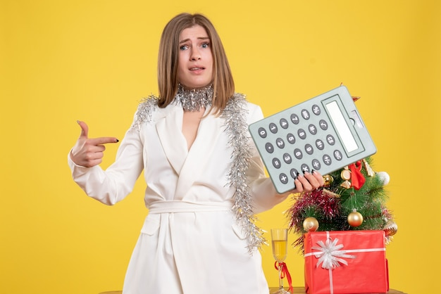 Front view female doctor standing and holding calculator on the yellow background with christmas tree and gift boxes Free Photo