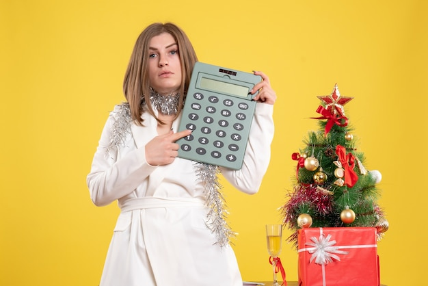 Front view female doctor standing and holding calculator on yellow background with christmas tree and gift boxes