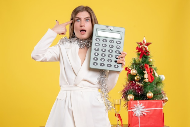 Front view female doctor standing and holding calculator on yellow background with christmas tree and gift boxes Free Photo