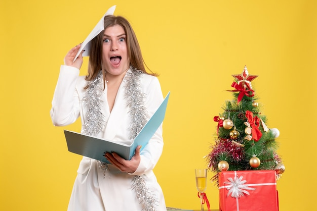 Front view female doctor standing and holding documents on a yellow background with christmas tree and gift boxes