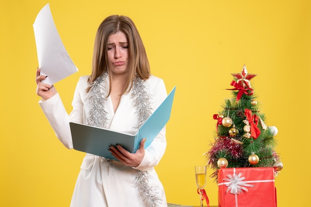 Front view female doctor standing and holding documents on the yellow background with christmas tree and gift boxes Free Photo