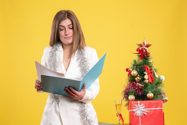 Medico femminile vista frontale in piedi e in possesso di documenti su sfondo giallo con albero di natale e confezioni regalo