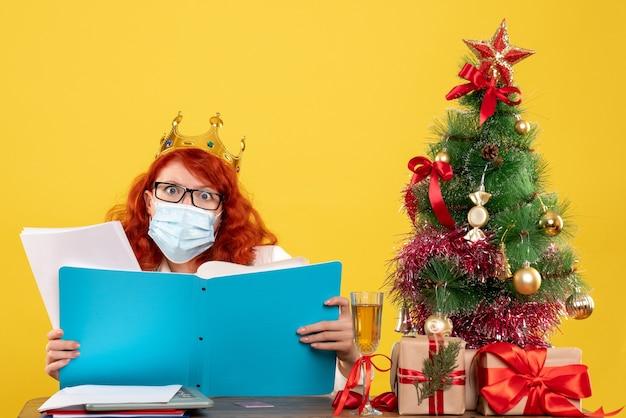Medico femminile di vista frontale nella mascherina sterile che controlla i documenti