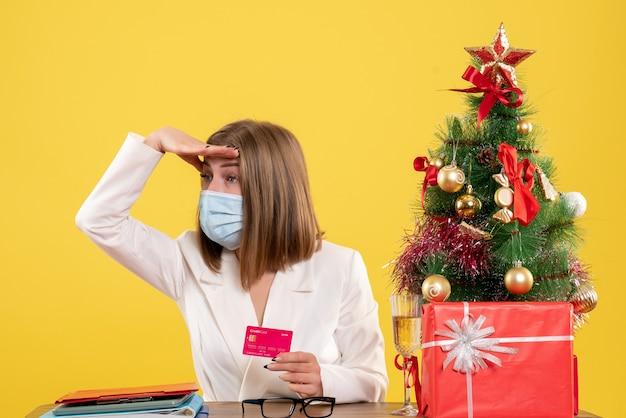 Medico femminile di vista frontale nella mascherina sterile che tiene la carta di credito