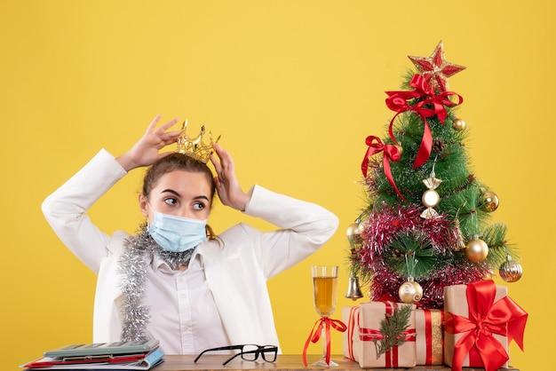 Medico femminile di vista frontale nella corona da portare sterile della mascherina