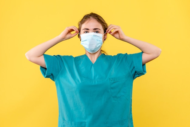 Front view female doctor in sterile mask on yellow background pandemic health virus covid
