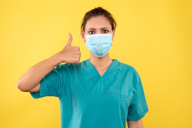 Front view female doctor in sterile mask on a yellow background