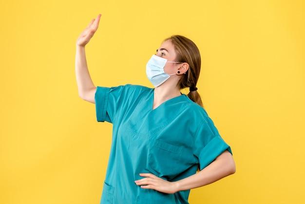 Medico femminile di vista frontale nella mascherina sterile sulla salute covid del virus pandemico dello scrittorio giallo