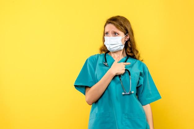 Vista frontale della dottoressa in maschera sterile sulla parete gialla