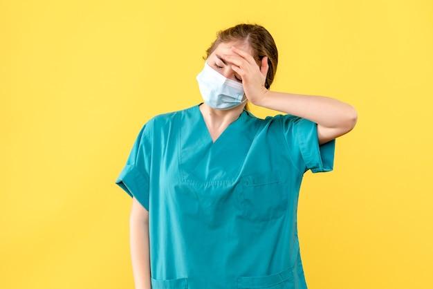 노란색 배경에 마스크에 강조 전면보기 여성 의사 건강 병원 covid 전염병