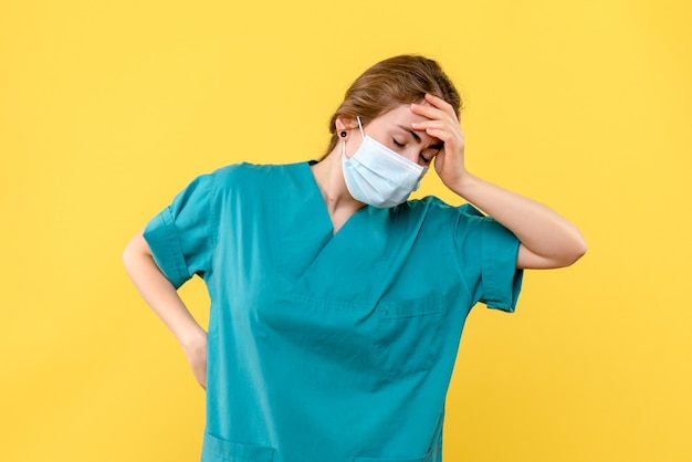 Front view female doctor stressed in mask on yellow background covid- health hospital pandemic