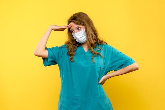 Vista frontale del medico femminile ha sottolineato nella maschera sulla parete gialla
