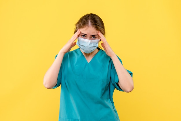 Вид спереди женщина-врач подчеркнула на желтом фоне пандемия здоровья больницы covid