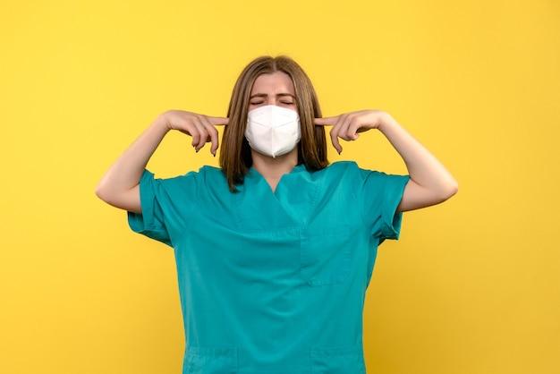 Medico femminile di vista frontale che stucking le sue orecchie sullo spazio giallo