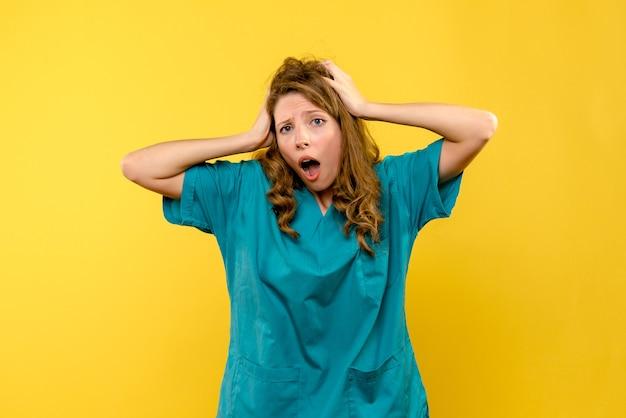 Medico femminile di vista frontale sorpreso sullo spazio giallo