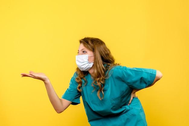 Vista frontale del medico femminile che parla con qualcuno sulla parete gialla