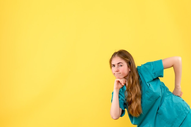 Front view female doctor thinking on yellow background health medic emotions hospital
