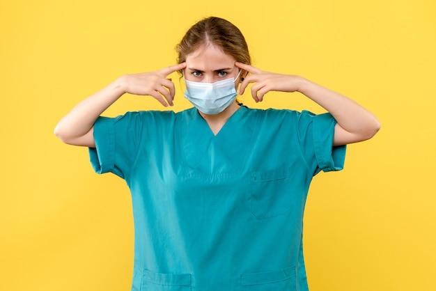 Medico femminile di vista frontale che pensa sulla pandemia di covid-pandemia dell'ospedale di sfondo giallo Foto Gratuite