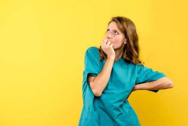 Vista frontale del medico femminile che pensa sulla parete gialla