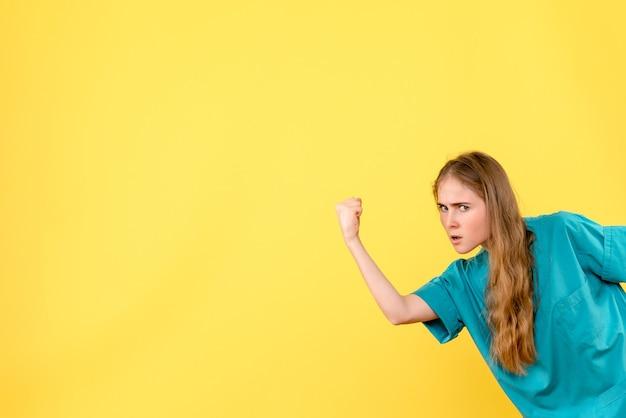 Medico femminile di vista frontale che minaccia sull'ospedale di emozione del medico di salute del fondo giallo