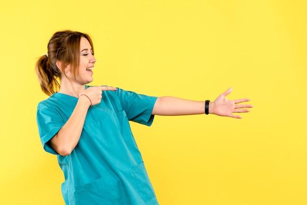 黄色い空間で握手しようとしている正面図の女医師