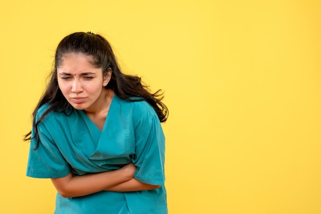 Medico femminile di vista frontale in uniforme che tiene il suo stomaco dolorante