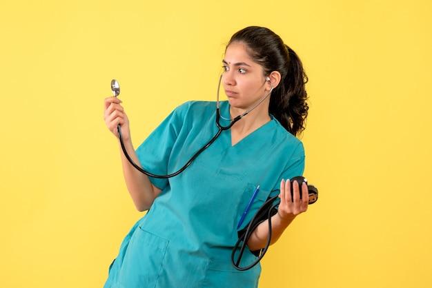Medico femminile di vista frontale in uniforme che tiene sfigmomanometri