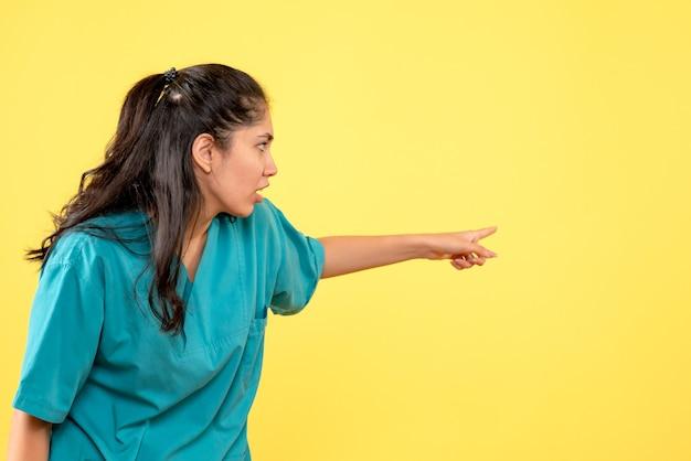 Medico femminile di vista frontale in uniforme che indica dietro