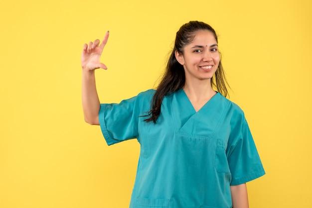 Medico femminile di vista frontale in uniforme che mostra le dimensioni con la mano in piedi
