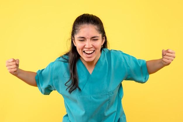Medico femminile di vista frontale in uniforme che mostra gesto vincente