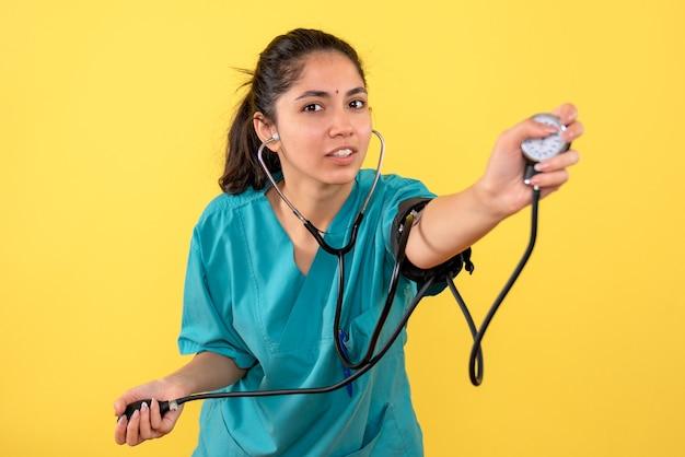 Medico femminile di vista frontale in uniforme utilizzando il dispositivo di misurazione della pressione sanguigna