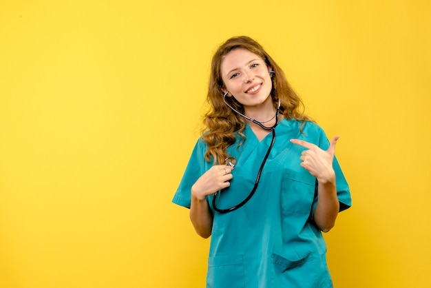 Front view female doctor using stethoscope on yellow space