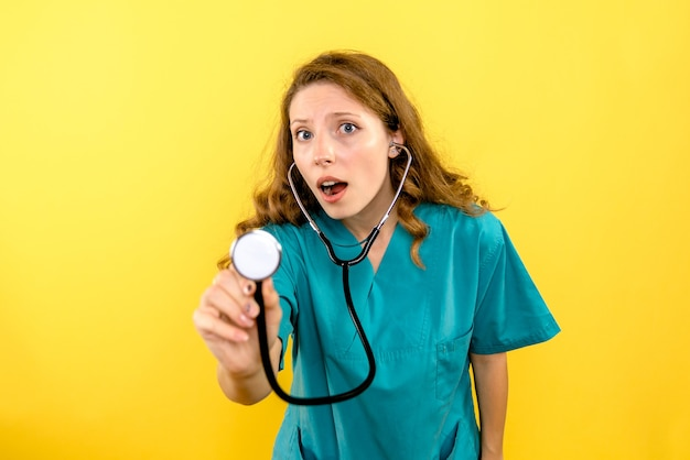 Front view of female doctor using stethoscope on yellow wall