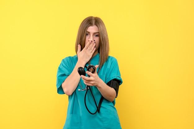 Medico femminile di vista frontale che per mezzo del tonometro su spazio giallo