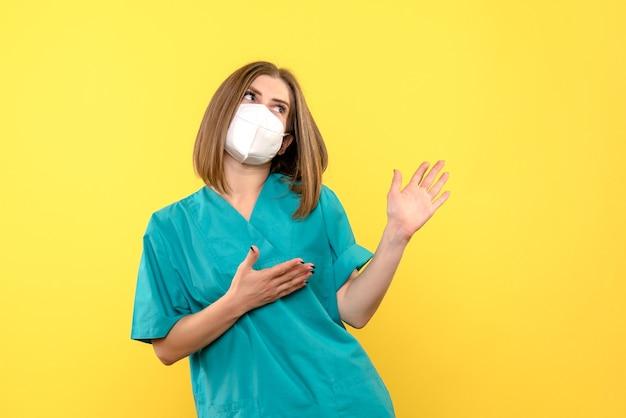 노란색 공간에 마스크를 쓰고 전면보기 여성 의사