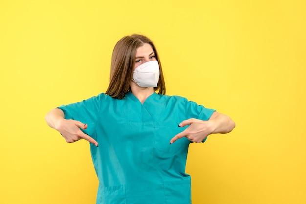 黄色いスペースにマスクを身に着けている正面図の女性医師
