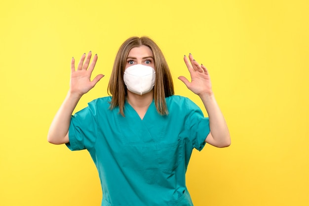 Front view female doctor wearing mask on yellow space