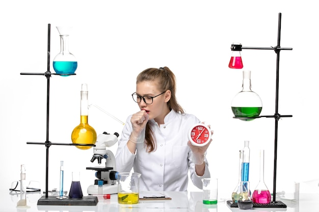 Front view female doctor in white medical suit holding clocks and coughing on white background virus chemistry pandemic covid