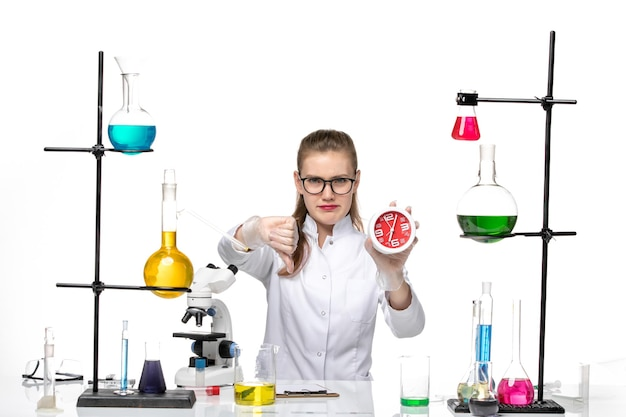 Front view female doctor in white medical suit holding clocks on light white background virus covid chemistry pandemic