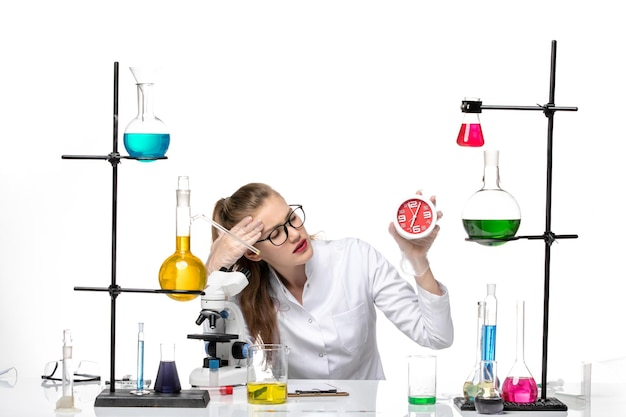 Front view female doctor in white medical suit holding clocks on a white background virus covid chemistry pandemic