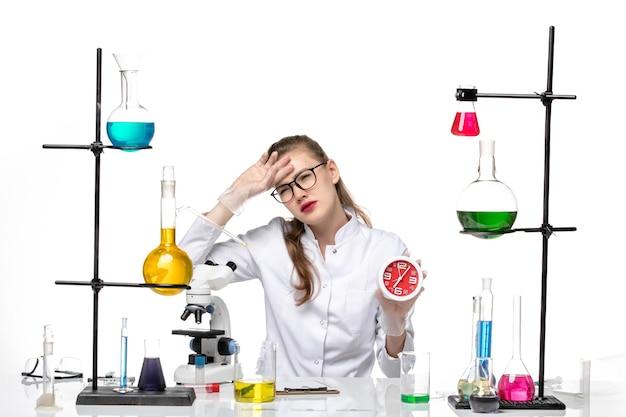 Medico femminile di vista frontale in vestito medico bianco che tiene gli orologi sul covid pandemia di chimica del virus della scrivania bianca