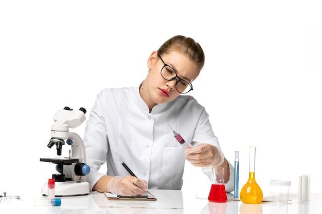 Medico femminile di vista frontale in vestito medico bianco che tiene iniezione sullo scrittorio bianco chiaro